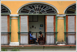 Family sitting near an open window, Plaza de Armas, Old Havana.