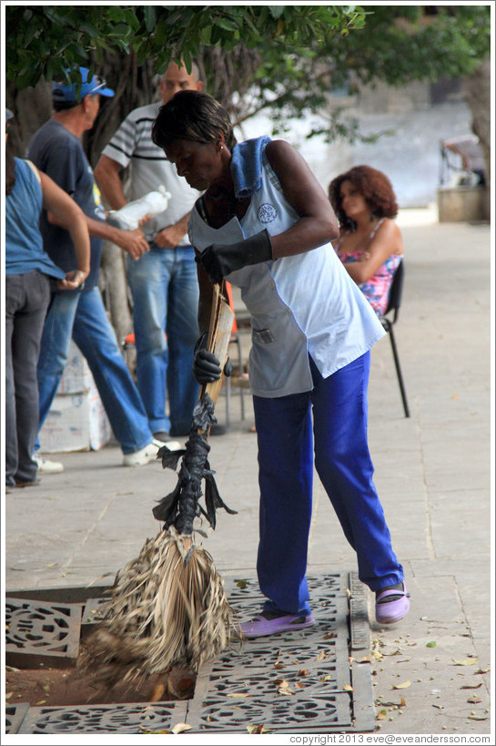 Woman sweeping using a broom made of plant fronds, Plaza de Armas, Old Havana.