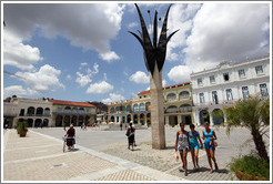 Three women passing a flower sculpture, Plaza Vieja, Old Havana.