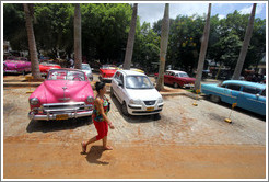 Woman walking past a hot pink car, Paseo del Prado.
