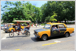 Bicycle taxi and black and white auto taxi, corner of Paseo del Prado and Calle Obrapia.
