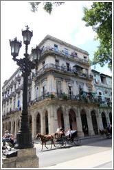 Horse drawn carriage passing a beige building, Paseo del Prado.