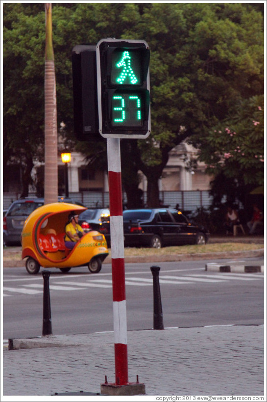 Walk sign with a countdown of remaining seconds, and a Coco taxi, Paseo del Prado.