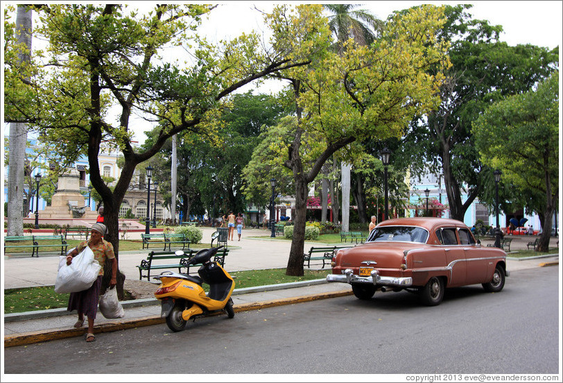 Woman carrying bags next to a yellow scooter and red car, Parque de la Libertad (Liberty Park).