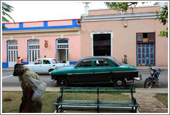 Homeless man and dark green car, near Parque de la Libertad (Liberty Park).
