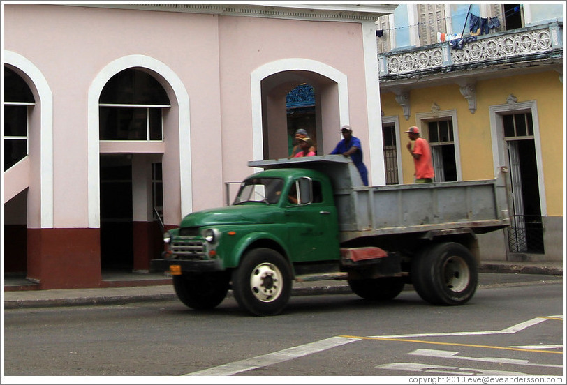 Truck with people standing in it passing Teatro Velasco, near Parque de la Libertad (Liberty Park).