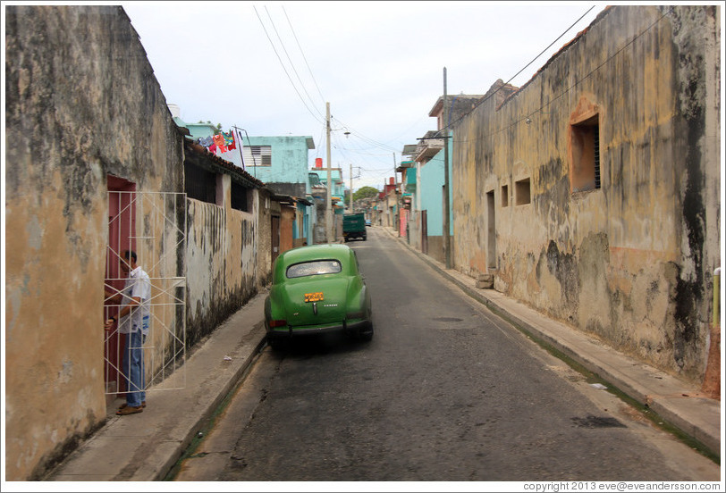 Street with green car.