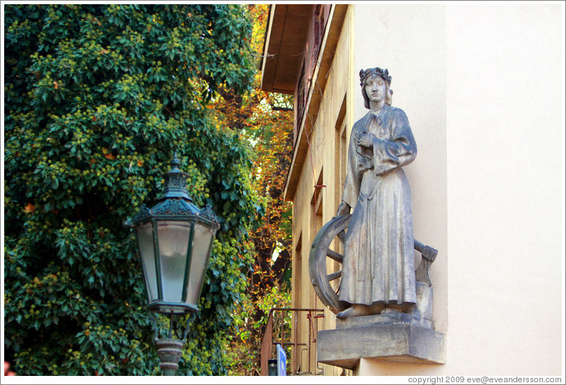 Sculpture of a woman with a wheel and an axe, on the side of a building, Kampa, Mal?trana.