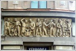 "Nine laborers, with the caption ""EXPORT IMPORT"" carved into a building on Pansk?Nov?ěsto."
