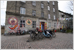 Paintings on a building, including a needle being broken, a woman with a Christiania flag, and a marijuana leaf.
