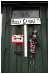 "Door with sign saying ""Hvor er Gandalf?"" (""Where is Gandalf?""), another saying ""langt ude"" (""long way""), a doll in a gas mask, and a 3rd sign saying ""Please do not attempt to walk on the water""."