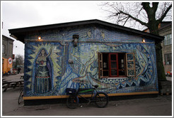 "House painted with a strong female figure and ""To exist is to Resist""."