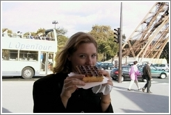 Eve, enjoying a waffle with nutella, in front of the Eiffel Tower.