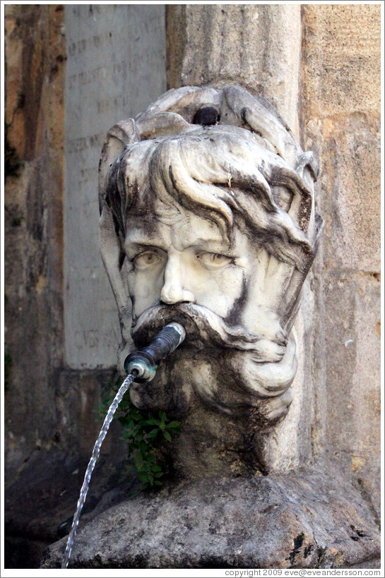 Face Containing A Water Spout Fountain In The Place De L