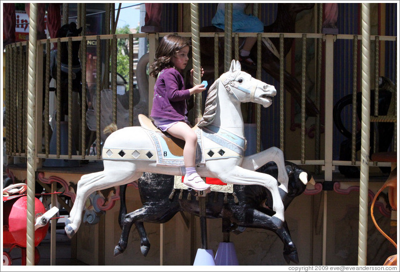 Girl riding a horse on the merry-go-round.  Place de la Rotonde.