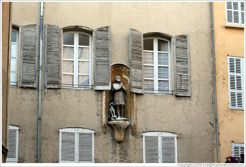 Oratory depicting a man and a dog.  A pigeon sits on the dog's head.  Rue Espariat at Rue de la Masse.  Old town.