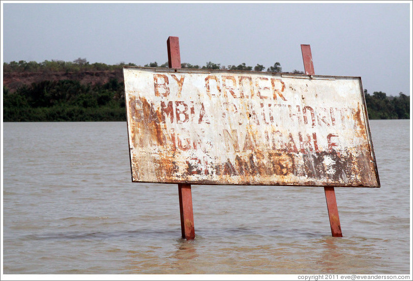 "Sign in the River Gambia near Baboon Islands, reading ""By order of Gambia P. Authority non-navigable channel."""