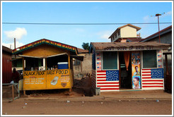 Two roadside shops Black Root Fast Food and Don't Give Up Hair Cut.  The latter is plastered with American flags.