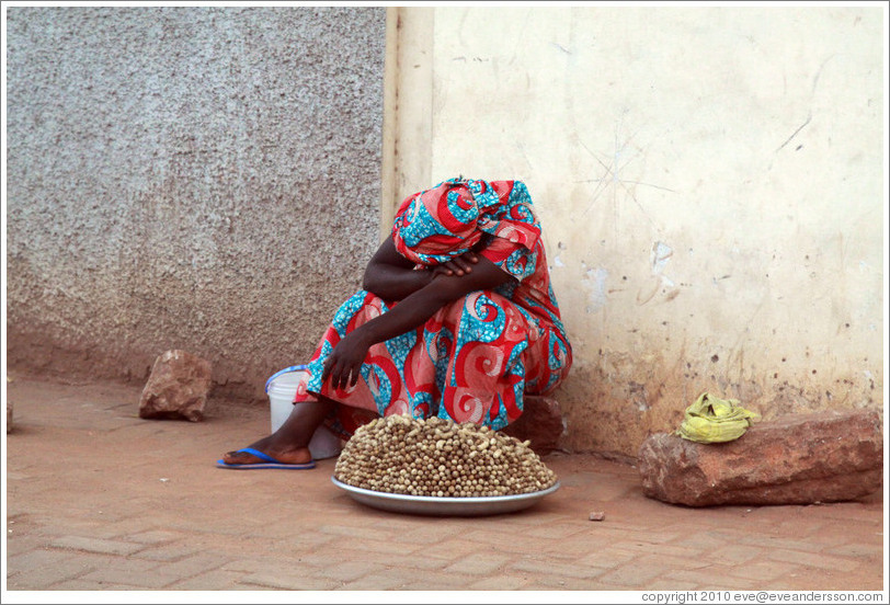Woman with peanuts for sale, resting.