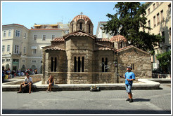 Man blowing bubbles in front of the Church of Panaghia Kapnikarea (Εκκλησία της Παναγίας Καπνικαρέας), one of the oldest churches in Athens.