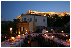 Ελαια restaurant.  Rooftop dining area with the Acropolis (Ακρόπολη) behind it, at night.