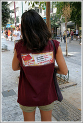 "Girl wearing a shirt for the Communist Youth of Greece. It says ""Πρωτοπόρα θεωρία Πρωτοπόρα δράση για το μέλλον μας το σοσιαλισμό,"" which translates as ""Pioneering theory Pioneering action for our future socialism."
