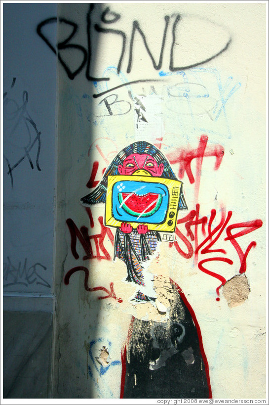 Graffiti depicting a girl holding a television set displaying a bitten watermelon slice.