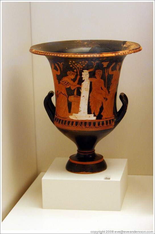 Calyx krater depicting a female figure adorning a herm with an altar in front of it and a nude man holding a spit for entrails from a sacrifice.  From 350-325 BC.  National Archaeological Museum.
