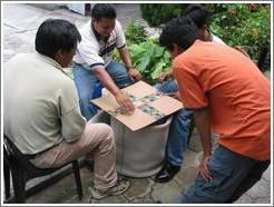 Guys playing a board game (basically: roll the dice and move forward that number of squares).