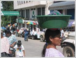 Woman carrying basket on head.