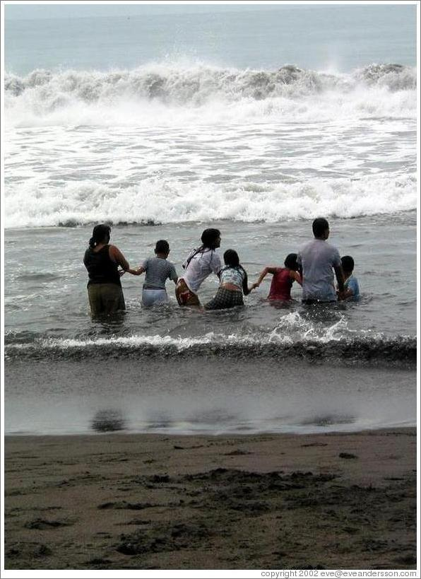 Monterrico beach.  Family enjoying the waves together.