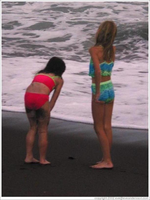 Two girls watching the baby turtles making their way to sea.