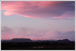 The glacier M?rdalsj?kull, appearing pink under a pink, dusky sky.
