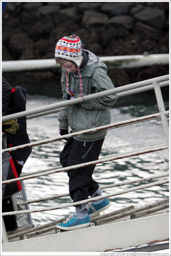 Child in Icelandic hat walking down ramp to boat.