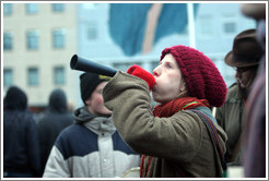 Reykjavik protest.  Woman blowing forn.