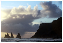 Reynisdrangar, volcanic rock shooting from the ocean, under the mountain Reynisfjall.