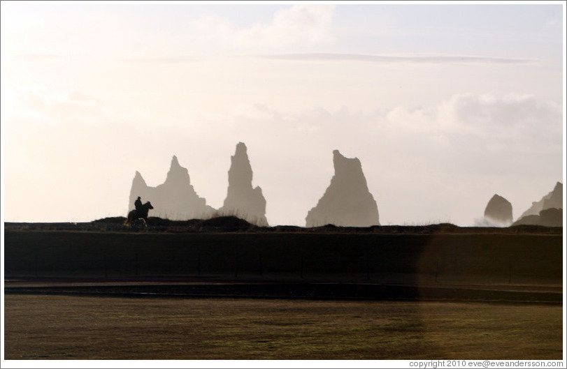 Reynisdrangar, volcanic rock shooting from the ocean, with a horseback rider passing in front.