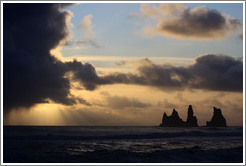 Reynisdrangar, volcanic rock shooting from the ocean, with the setting sun shining from behind clouds.