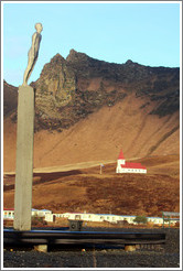 F?r (Voyage), a sculpture by Steinunn ?rarinsd?r (2006), with Vikurkirkja (Church of Vik) visible behind it.