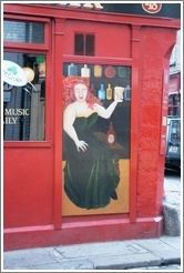 Painting of a fiery redhead enjoying the drink -- on a pub in Temple Bar, Dublin.