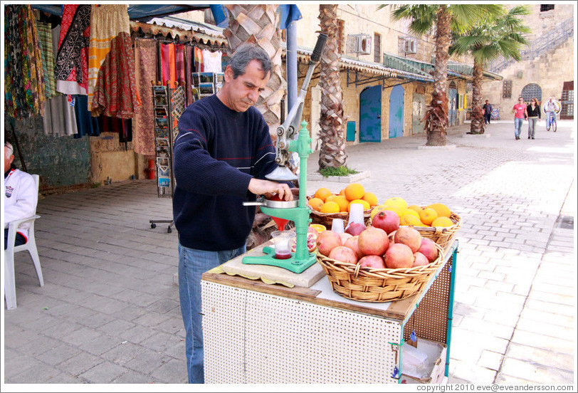 Man making pomegranate juice, old town Akko.