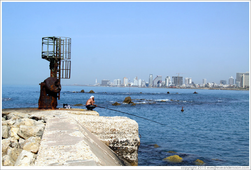 Man fishing, with Tel Aviv behind him.