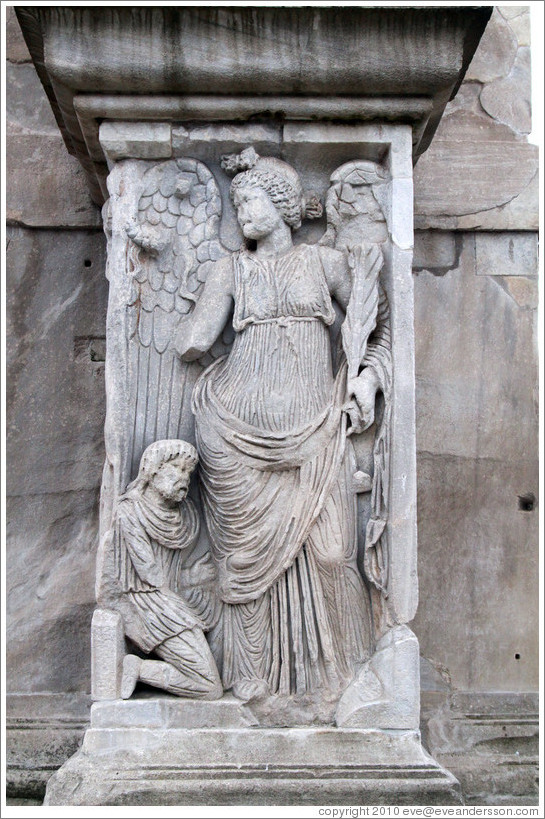 Slave kneeling before an angel.  Arco di Costantino (Arch of Constantine).