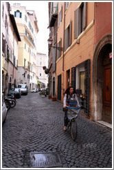 Woman riding bicycle on Via del Pellegrino.