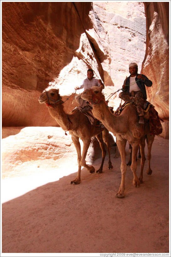 Two men riding camels in As-Siq, a narrow natural gorge.