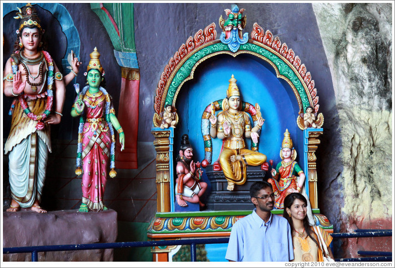 Two people in front of statues, Batu Caves.