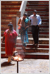 People descending steps toward fire, Batu Caves.