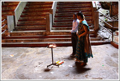 Man and woman in front of fire, Batu Caves.