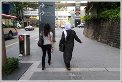 Two women walking down Jalan Raja Chulan.