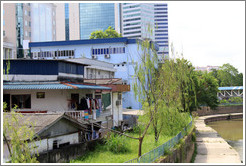 House with hanging clothes in front of a skyscraper on the bank of the Sungai Kelang, near Jalan Dang Wangi.
